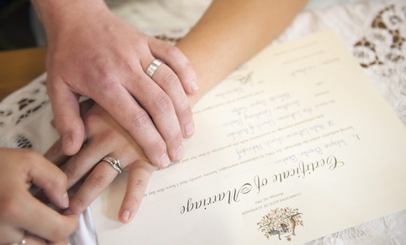 Hands on wedding certificate
