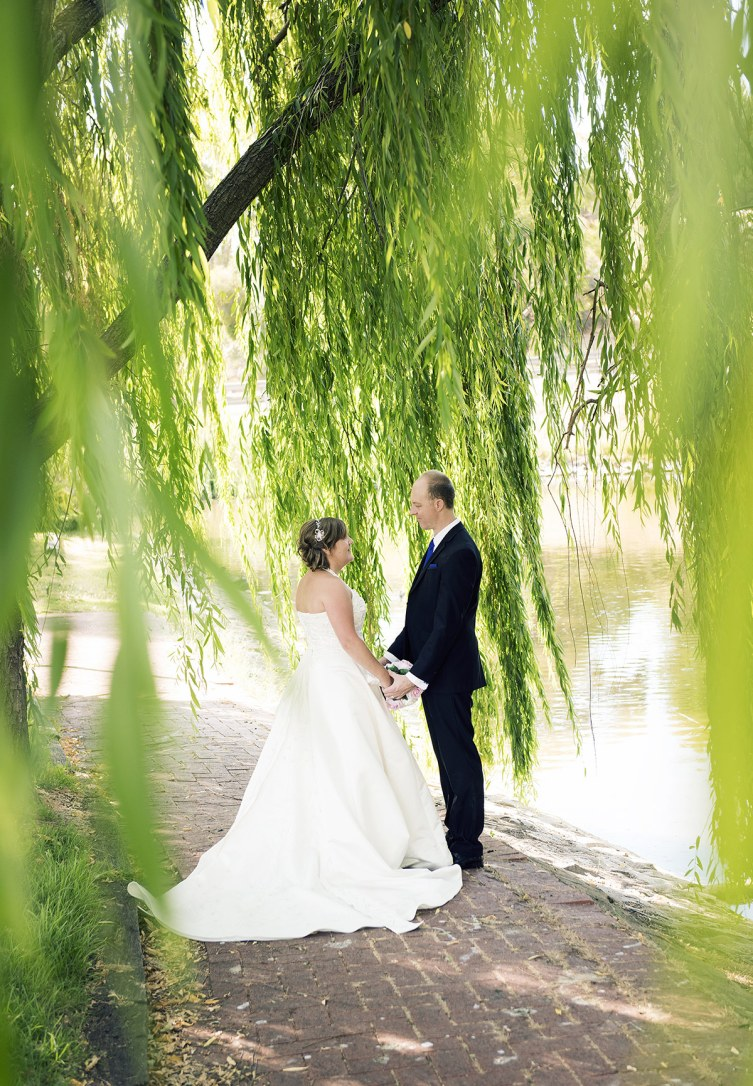 Bride and groom under willow trees