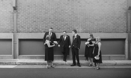 Bridal party on brick wall