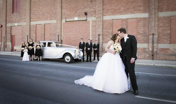 Bridal party with wedding car