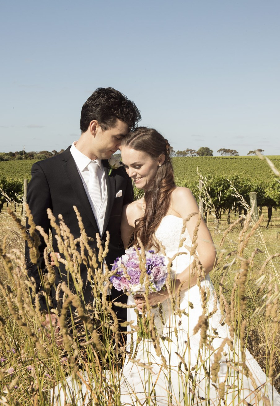 Bride and groom in long grass