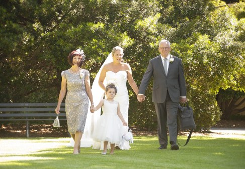 Bride and parents walking down the aisle