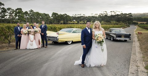 Bridal party in front of cars