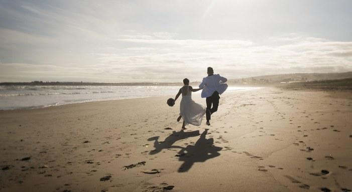bridal couple running on Middleton beach
