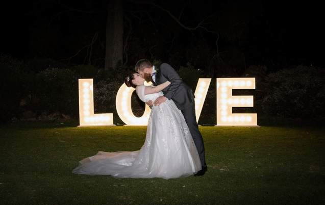 dancing in front of love sign