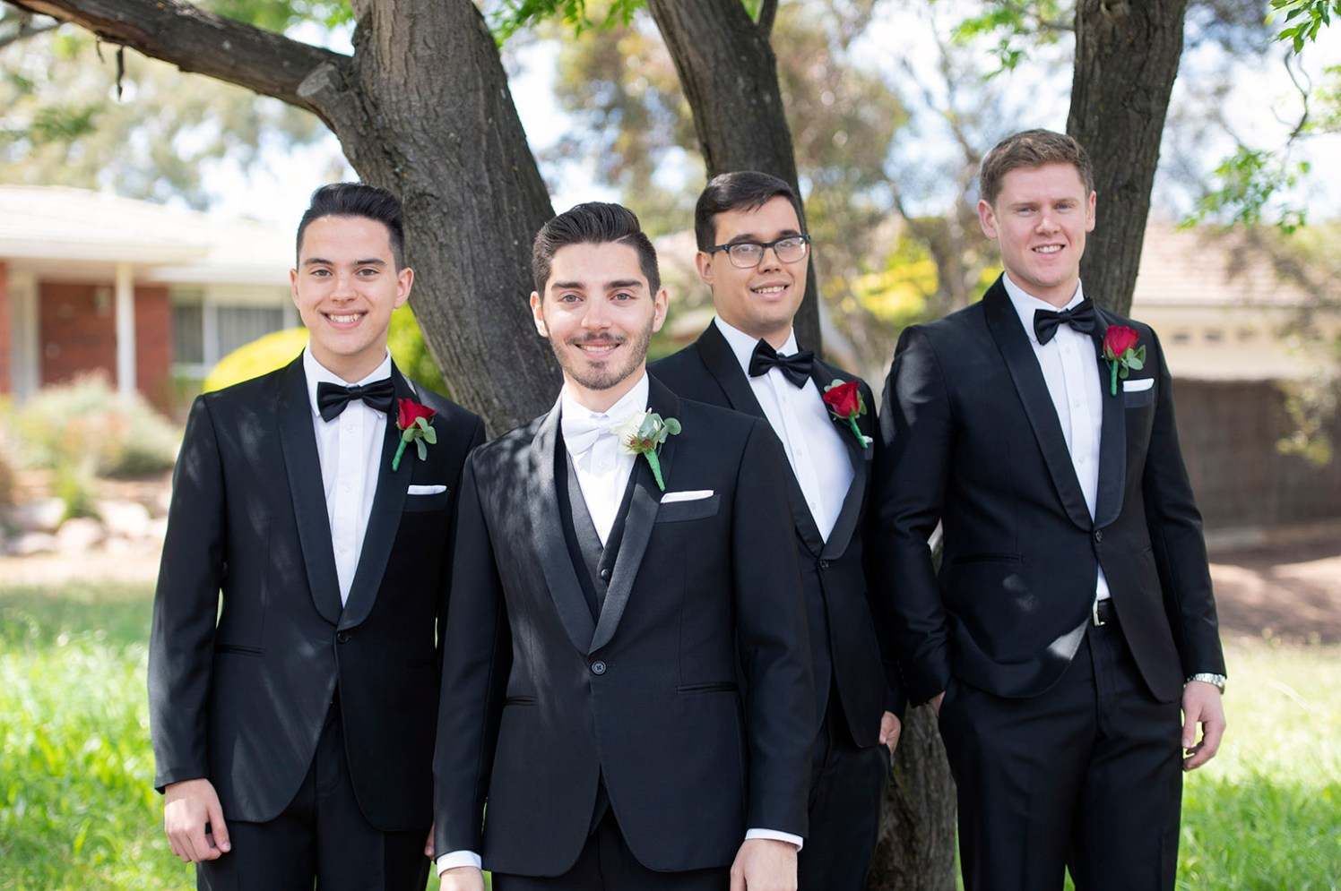 Groom and groomsmen standing under tree