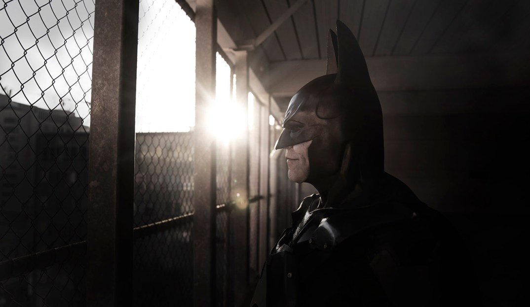 Batman cosplay looking out parking lot
