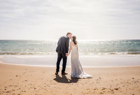 Bridal couple kissing on the beach