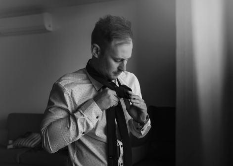 Tieing tie in front of window