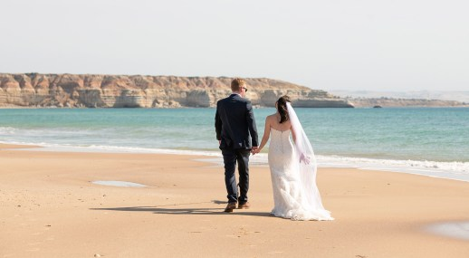 Wedding couple walking along the beach