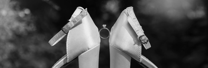 Engagement ring in between wedding shoes