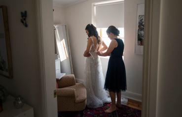 Helping put on wedding dress
