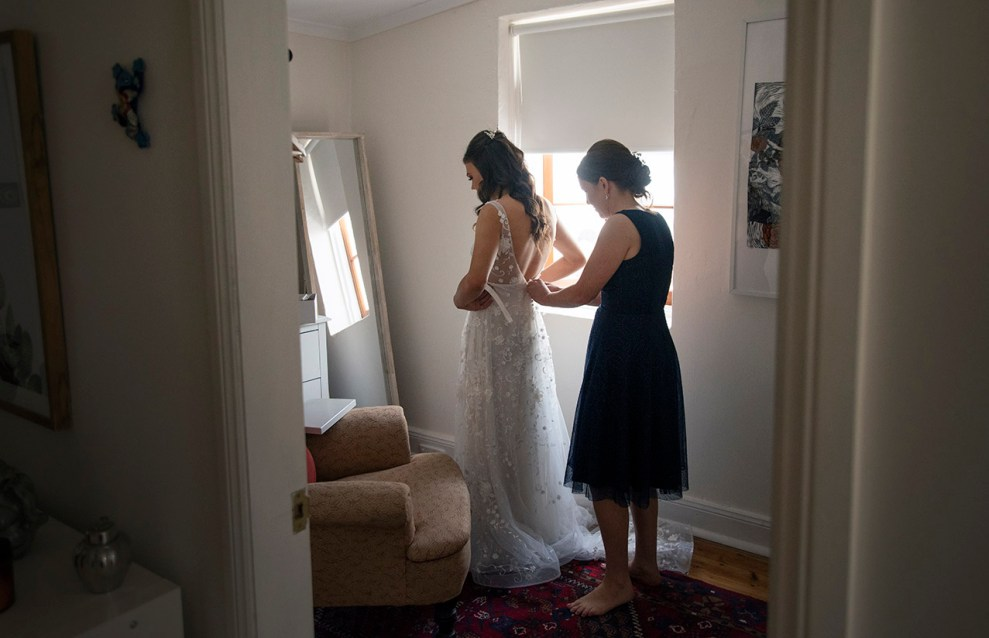 Helping put on wedding dress