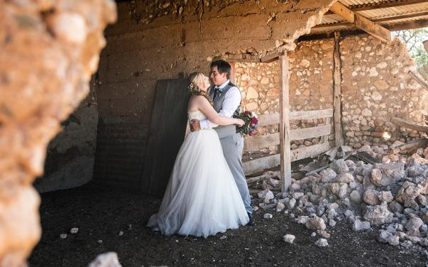 Bride and groom hugging in ruin