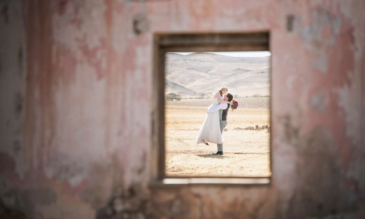 Groom picking up bride through window