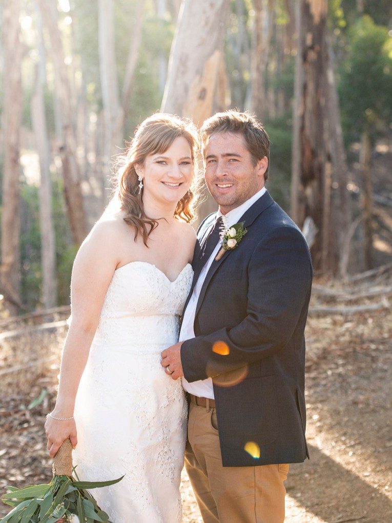Bride and groom standing together in forest