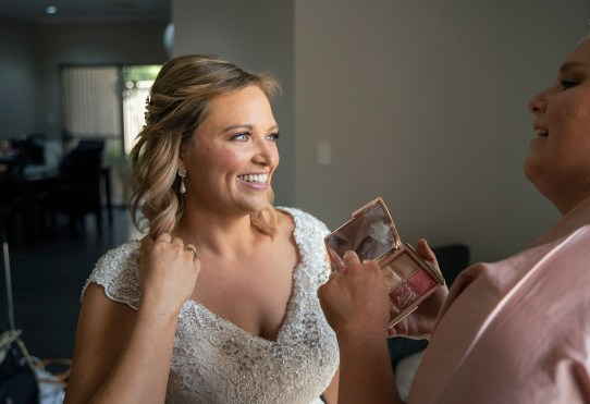 smiling bride as she gets ready