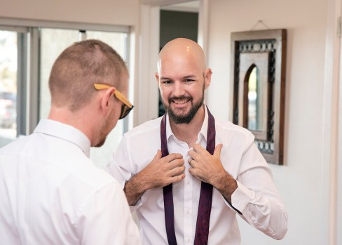 Smiling groomsmen putting on tie