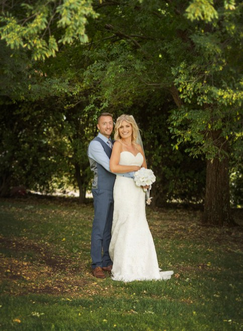 Bride and groom holding one another in the trees