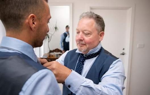 Groomsman helping put on grooms tie