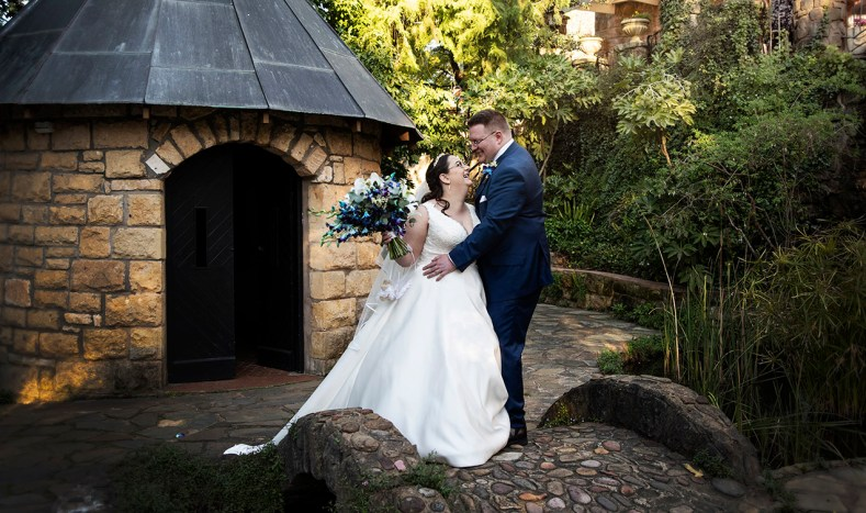 Bride and groom in front of the manor basket range's chapel