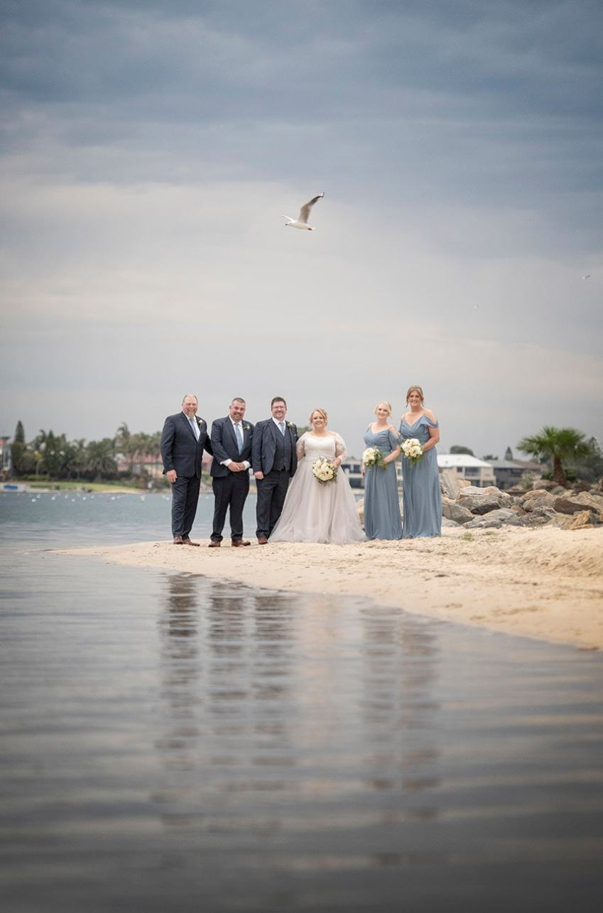 bridal party standing on the beach near the Lakes Hotel