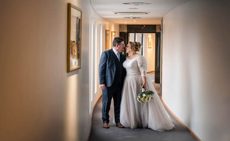 Bride and groom walking down hallway at the Lakes Hotel