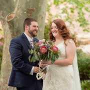 Bride and groom having fun under a tree
