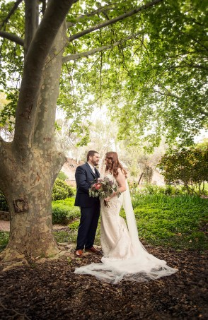 Bride and groom under the leaves at the Stockade Botanic Park