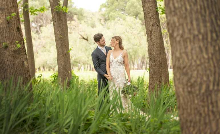 Bride and groom standing with each other in trees at Seppeltsfield winery