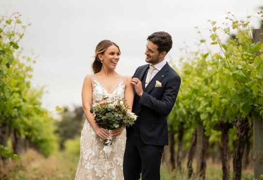 Groom surprising bride in vineyards