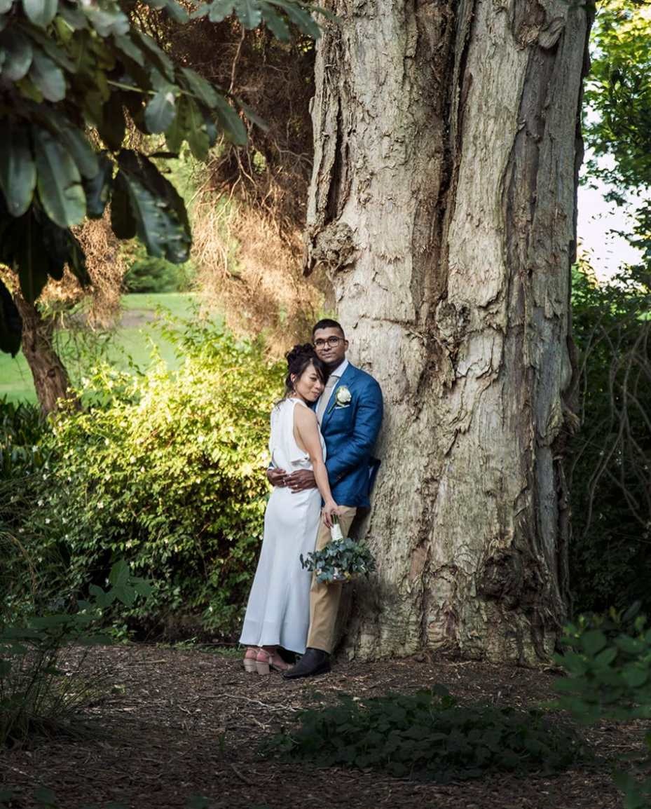 Bride and groom against a large tree