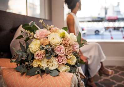 closeup of bouquet while bride looks out window
