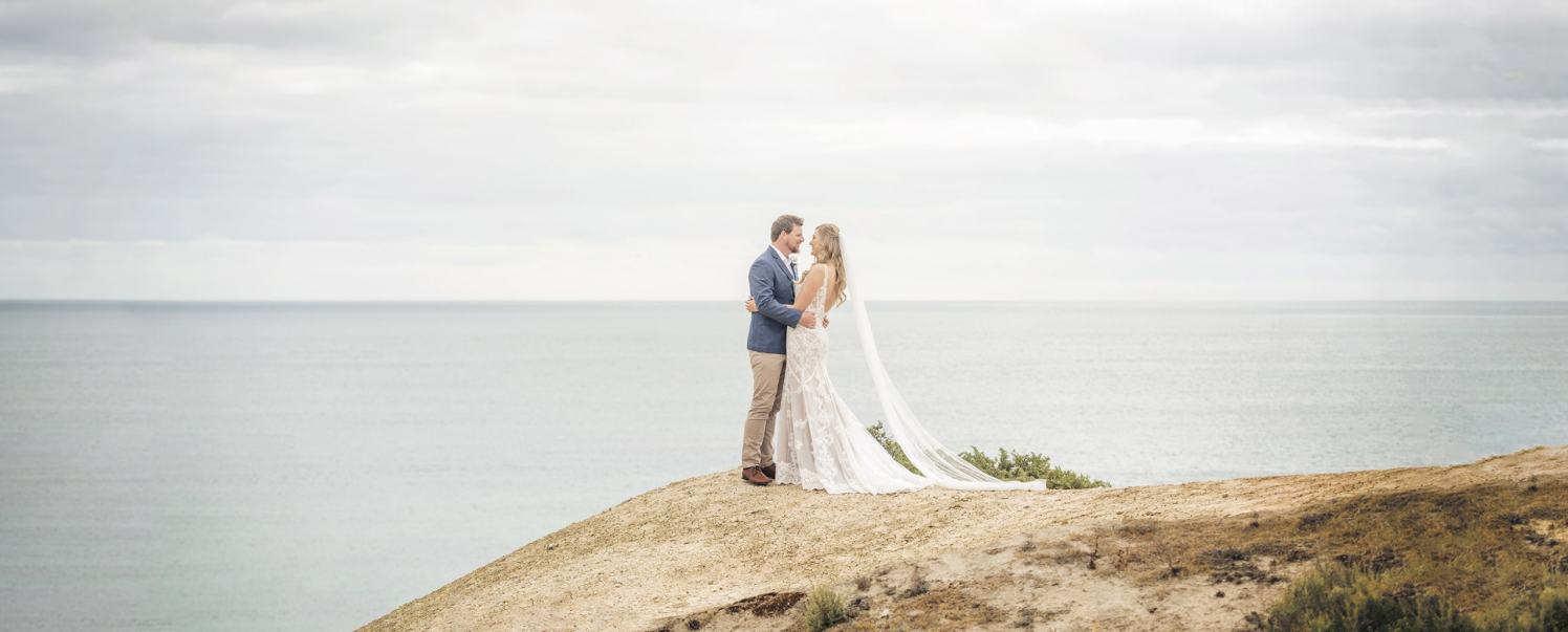 bride and groom on hill over ocean