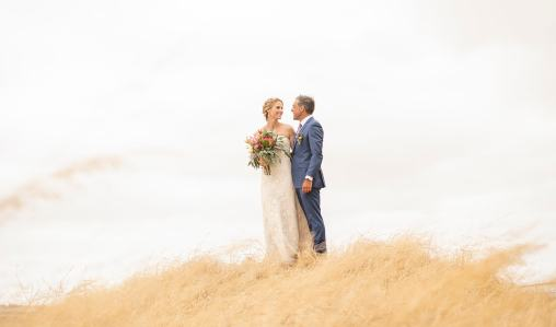 bride and groom on the top of a grassy hill