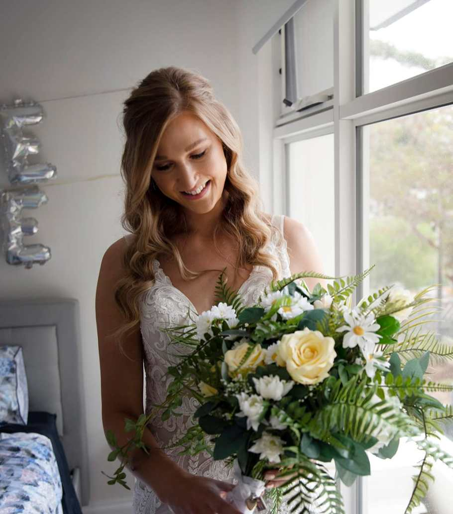Bride holding her bouquet next to window