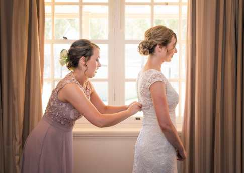 Bridesmaid helping with lacing up wedding dress