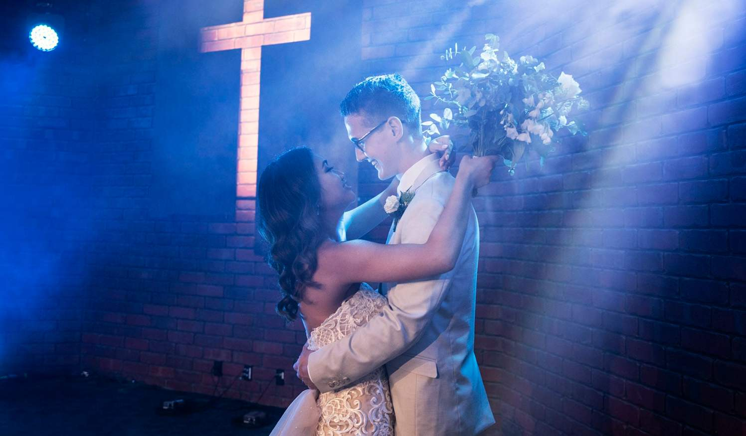 bride and groom under blue lights and smoke