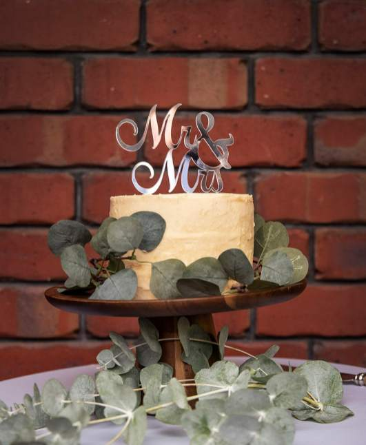 Wedding cake in front of brick wall