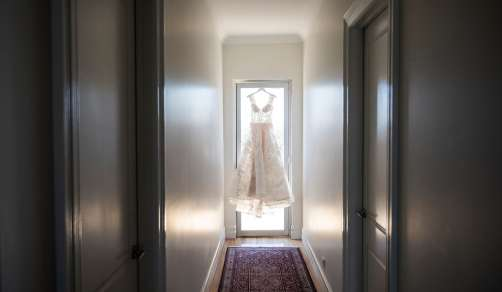 Wedding dress hanging at end of hall
