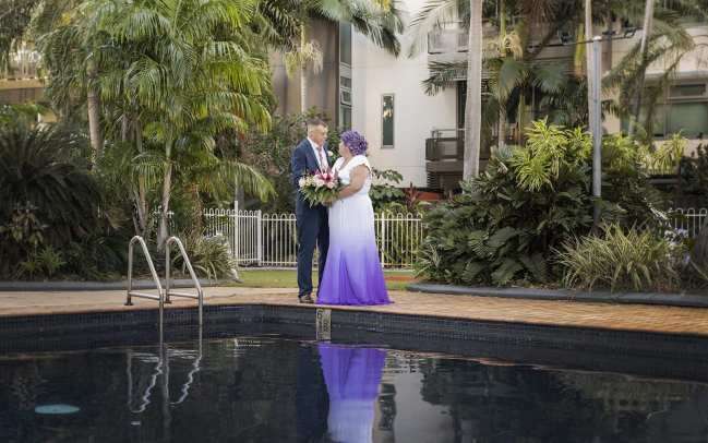 bride and groom on the pool edge