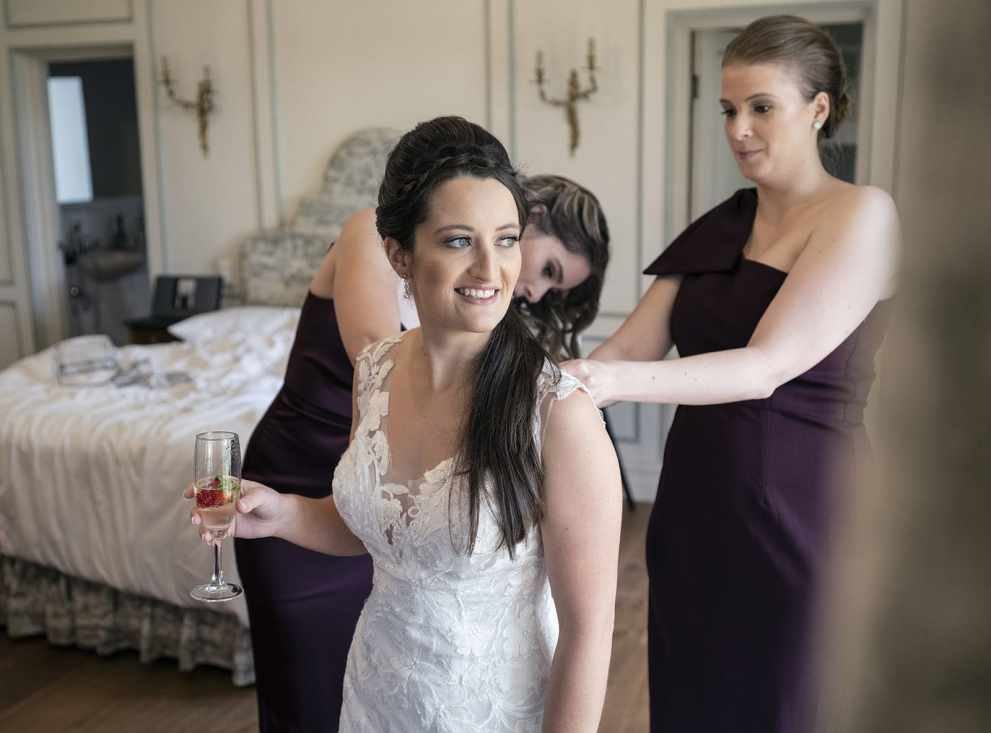 bride having a wine while getting dressed