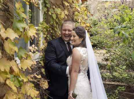 Laughing bride and groom amongst ivy