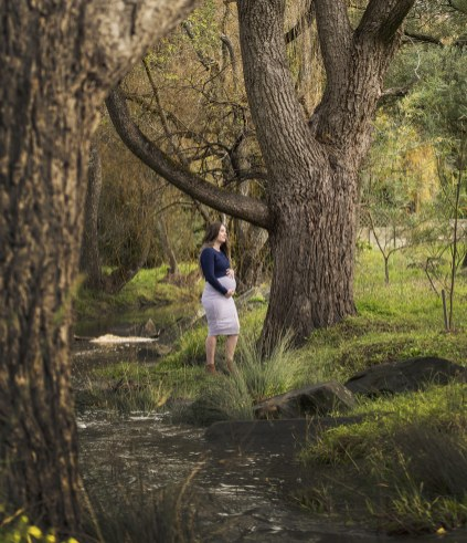Mother to be standing in forrest