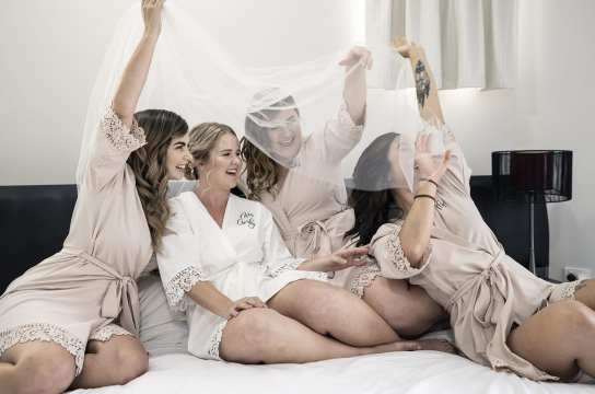 Bride and bridesmaids having fun under veil on bed