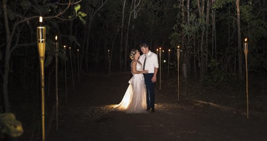 bride and groom between the tiki torches