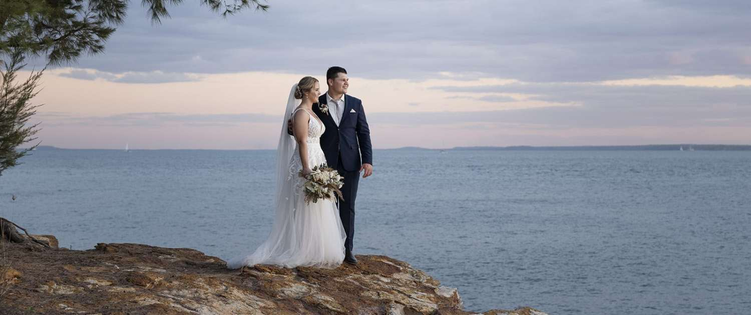 bride and groom looking out at the sunset