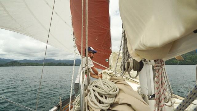 Sailing into Bahia Honda, Jon folding the yankee sail