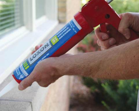 A paint contractor applying Loxon Sealant to a masonry window frame