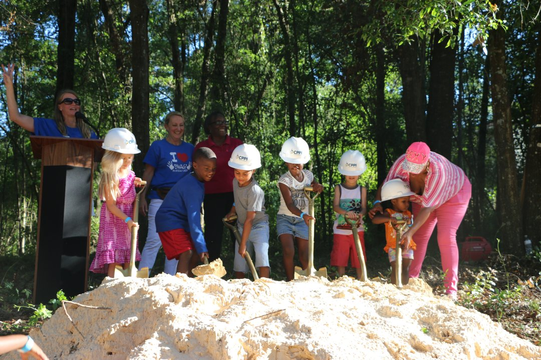 Six children start digging at the site of the future CHILD Center facility. The smallest receives help from an adult.